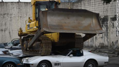 TOPSHOT - A bulldozer crushes luxury vehicles at a ceremony at the customs yard in Manila on February 6, 2018, after they were seized for being smuggled illegally. President Duterte watched bulldozers flatten dozens of sports cars and other luxury vehicles February 6 as part of a drive to fight corruption at the country's customs bureau. / AFP PHOTO / TED ALJIBE        (Photo credit should read TED ALJIBE/AFP/Getty Images)