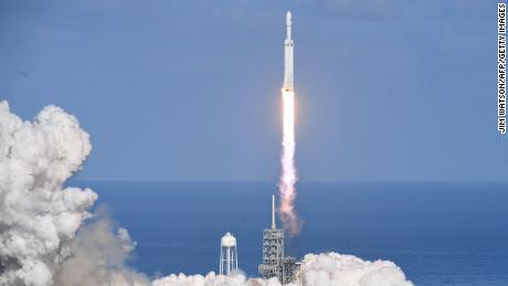 The SpaceX Falcon Heavy takes off from Pad 39A at the Kennedy Space Center in Florida, on February 6, 2018, on its demonstration mission. The world's most powerful rocket, SpaceX's Falcon Heavy, blasted off Tuesday on its highly anticipated maiden test flight, carrying CEO Elon Musk's cherry red Tesla roadster to an orbit near Mars. Screams and cheers erupted at Cape Canaveral, Florida as the massive rocket fired its 27 engines and rumbled into the blue sky over the same NASA launchpad that served as a base for the US missions to Moon four decades ago.  / AFP PHOTO / JIM WATSON        (Photo credit should read JIM WATSON/AFP/Getty Images)