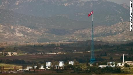 A North Korean flag flutters over North Korea's village of Gijungdong as seen from an observatory point in Paju near the Demilitarized Zone (DMZ) dividing the two Koreas on September 25, 2013. The 250-kilometre (155-mile) long Demilitarised Zone dividing the two neighbours is a depopulated no-man's land bristling with landmines and listening posts.   AFP PHOTO / KIM DOO-HO        (Photo credit should read KIM DOO-HO/AFP/Getty Images)