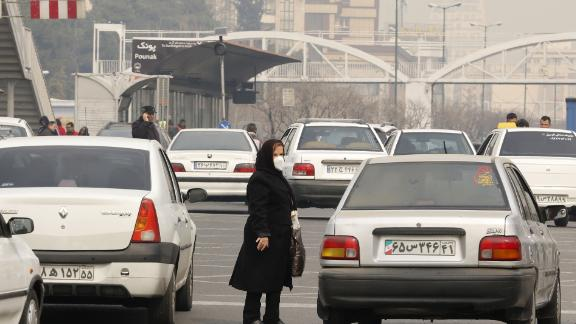 An Iranian woman wearing a face mask waits at a bus stop as heavy pollution hit new highs in Tehran on February 5, 2018.  (Photo credit:  ATTA KENARE/AFP/Getty Images)