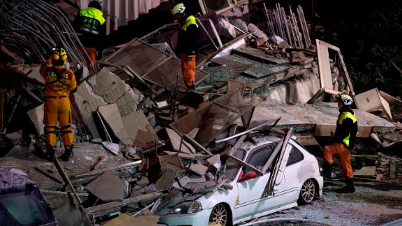 Members of the emergency services search for people in the debris of a collapsed building.