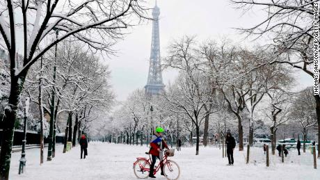 People walk through the snow covered alley of the Champ de Mars following heavy snowfall in Paris, on February 7, 2018 near the Eiffel tower.
