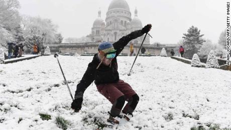 A man is skiing on the snow-covered Montmartre hill in front of the Basilica of the Sacred Heart (Basilique du Sacre-Cur) on February 6, 2018 in Paris. 