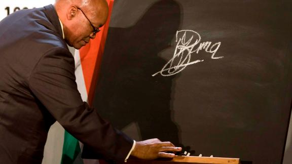 Zuma signs a blackboard in October 2009, pledging South Africa
