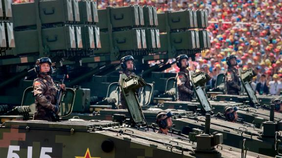 Chinese soldiers ride on armored missile carriers as they pass in front of Tiananmen Square and the Forbidden City during a military parade on September 3, 2015, in Beijing.