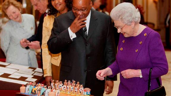 Zuma looks at a chess set with Britain's Queen Elizabeth II during his state visit in 2010. The chess set had been given to the Queen by Nelson Mandela in 1996.