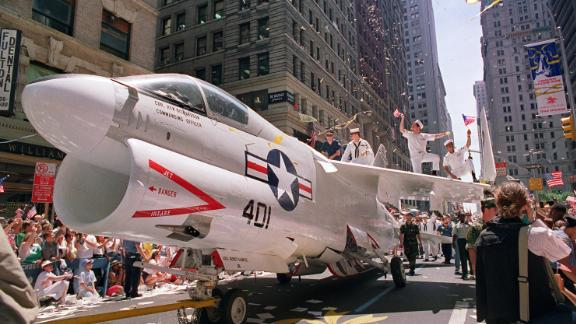 A Navy A-7 Corsair jet is pulled down Broadway Avenue as sailors rejoice on the wings during the Operation Welcome Home ticker-tape  parade during the 10 June 1991 celebration for returning Gulf War troops.  An estimated 1 million people came to welcome some 24,000 Desert Storm veterans.       AFP PHOTO DON EMMERT        (Photo credit should read DON EMMERT/AFP/Getty Images)