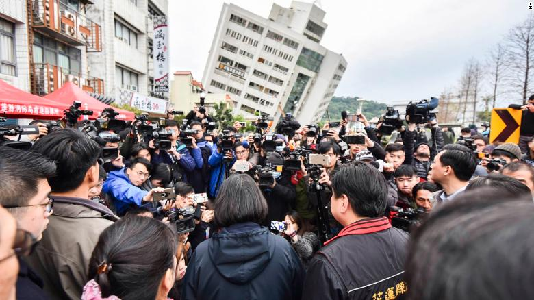 Taiwan's President Tsai Ing-wen, center back-facing, is briefed at the site of a collapsed building from an earthquake on Wednesday.