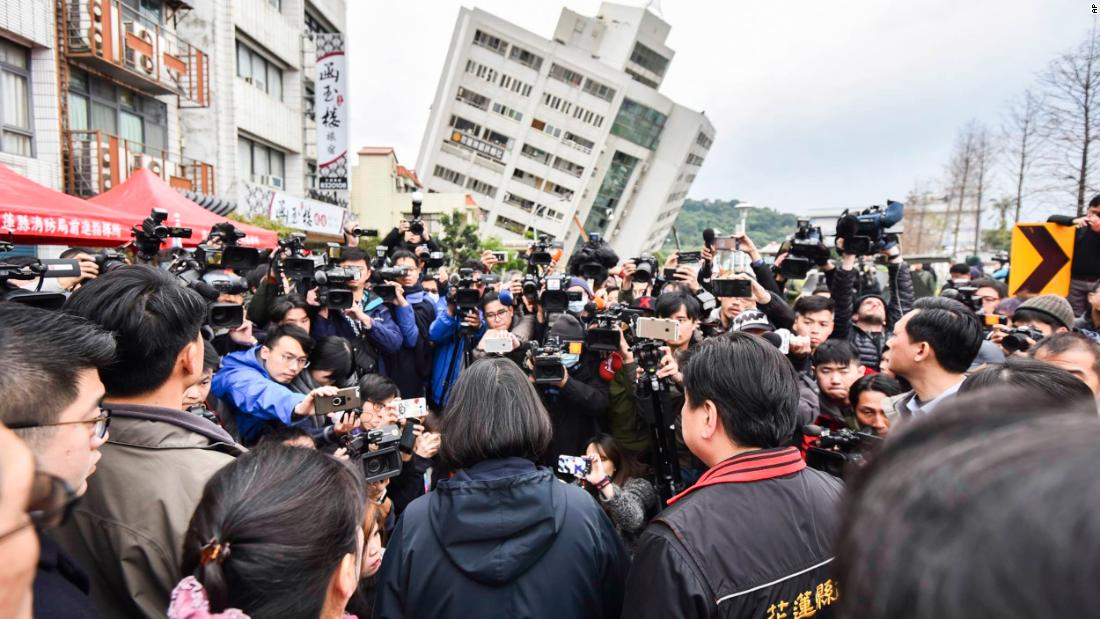 In this handout photo released by the Taiwan presidential office, President Tsai Ing-wen, center back-facing, is surrounded by media as she is briefed in Hualien on February 7.