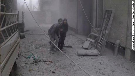 This photo provided by the Syrian Civil Defense group known as the White Helmets, shows two civilians fleeing from the scene of an attack after airstrikes hit a rebel-held suburb near Damascus, Syria, Monday, Feb. 5, 2018. Syrian opposition activists said more than one dozen people killed in new airstrikes. (Syrian Civil Defense White Helmets via AP)