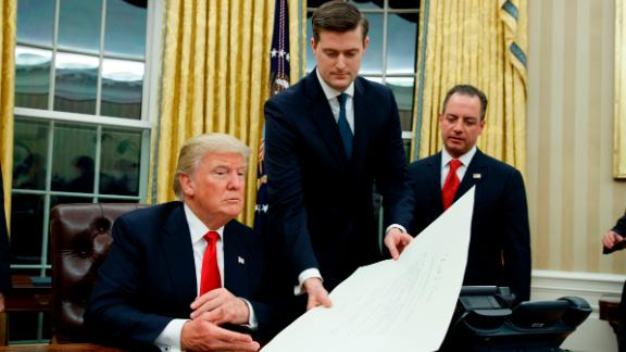 White House staff secretary, Rob Porter, center, works with President Donald Trump as Reince Priebus watches.