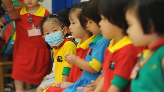 A masked girl sits with classmates at a kindergarten in a residential estate in Hong Kong on June 11, 2009. Hong Kong authorities on June 11 ordered all primary schools in the city to be closed for two weeks after the first cluster of local swine flu cases was found. The move came after 12 pupils at a city secondary school were found to have contracted the A(H1N1) virus, chief executive Donald Tsang told reporters. AFP PHOTO/MIKE CLARKE (Photo credit should read MIKE CLARKE/AFP/Getty Images)