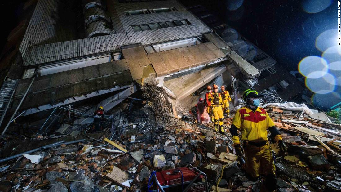 Rescue workers climb over debris at the Yun Tsui building.