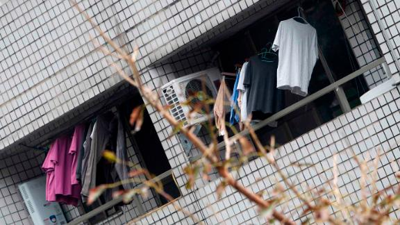 Clothes hang on the balcony of a leaning apartment building.