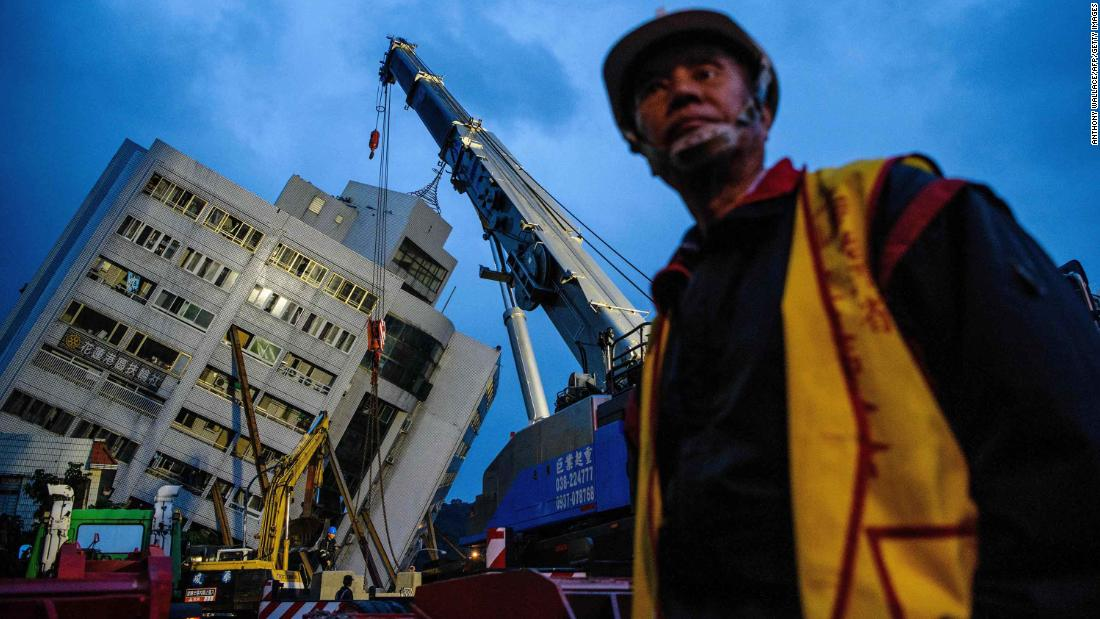 An emergency worker walks near a crane that was working to support the Yun Tsui building in Hualien. The residential building was shifted off its foundation during the quake.