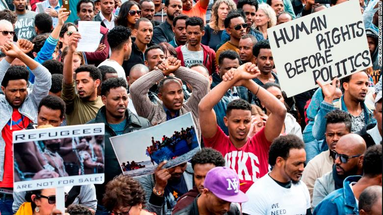 African migrants demonstrate with their hands crossed outside the Embassy of Rwanda in the Israeli city of Herzliya on February 7, 2018.