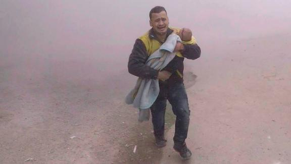 In a White Helmets photo, a paramedic flees with his wounded son after airstrikes near Damascus.