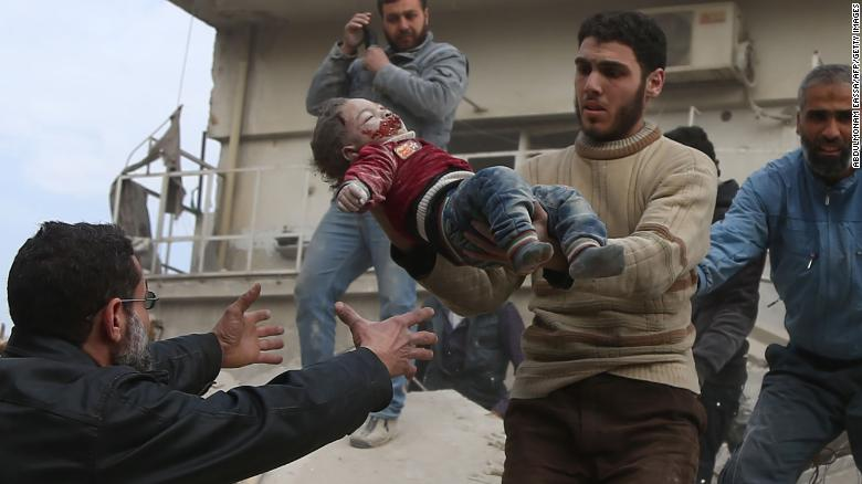 A man hands over a child to his father after being rescued from the ruins of a building in Eastern Ghouta on Tuesday.