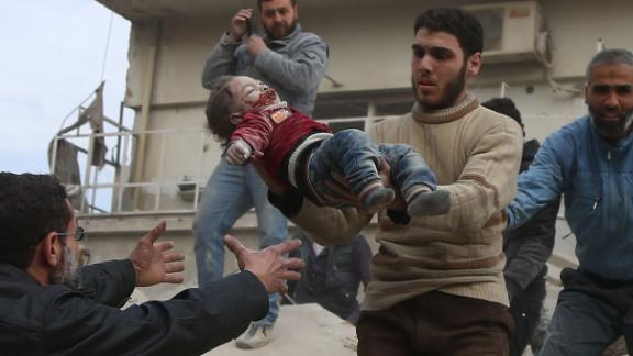 A wounded child is rescued from the ruins of a collapsed building after strikes Tuesday in Saqba.