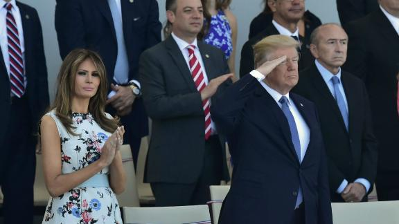 US President Donald Trump (2nd L) salutes as French President Emmanuel Macron (2nd R) his wife Brigitte Macron (R) and US First Lady Melania Trump (L) watch the annual Bastille Day military parade on the Champs-Elysees avenue in Paris on July 14, 2017. The parade on Paris