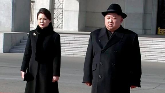 North Korean leader Kim Jong Un, right, and his wife Ri Sol Ju arrive at the parade
