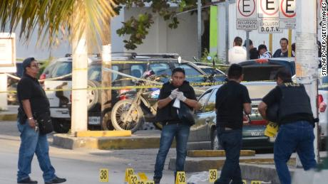Police investigators work on the crime scene where a shooting erupted after an attack against the building of the Quintana Roo State Prosecution, in Cancun, Mexico, on January 17, 2017.  The shooting happened as Mexican authorities investigate whether a feud over local drug sales was behind a nightclub shooting that killed three foreigners and two Mexicans Monday at the Blue Parrot club during the BPM electronic music festival in Playa del Carmen, a usually peaceful Caribbean seaside town. / AFP / STR        (Photo credit should read STR/AFP/Getty Images)
