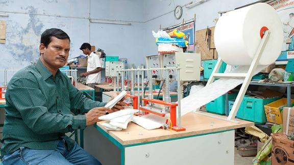 """India's """"menstrual man,"""" Arunachalam Muruganantham, shows off the $1,012 machine he designed to produce affordable sanitary pads."""