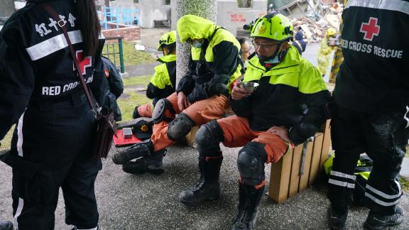 Rescuers rest near the site of damaged buildings in Hualien on February 8.