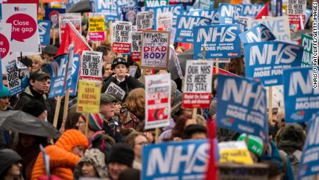 Demonstrators carry placards during a protest against the government's health policy on February 3 in London.