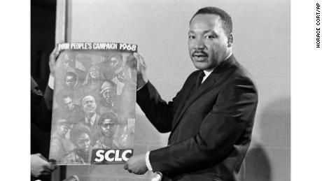The Rev. Martin Luther King Jr. displays the poster for his 1968 Poor People's Campaign.