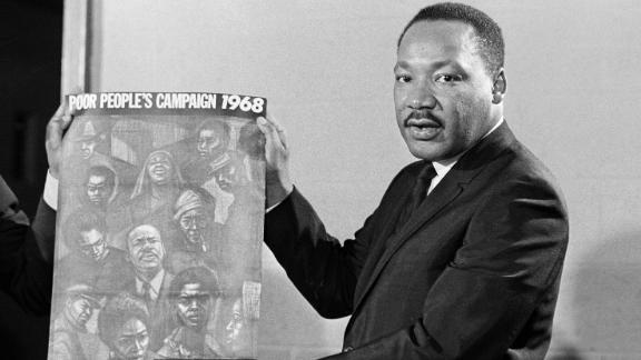 Dr. Martin Luther King displays the poster to be used during his Poor People