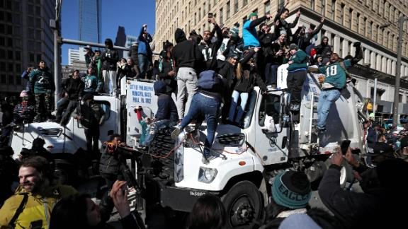 Fans fill the streets as they climb on trash trucks and celebrate with the Philadelphia Eagles.