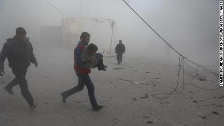 Syrian Arab Red Crescent workers try to rescue the wounded Thursday after an airstrike in Douma, Syria.