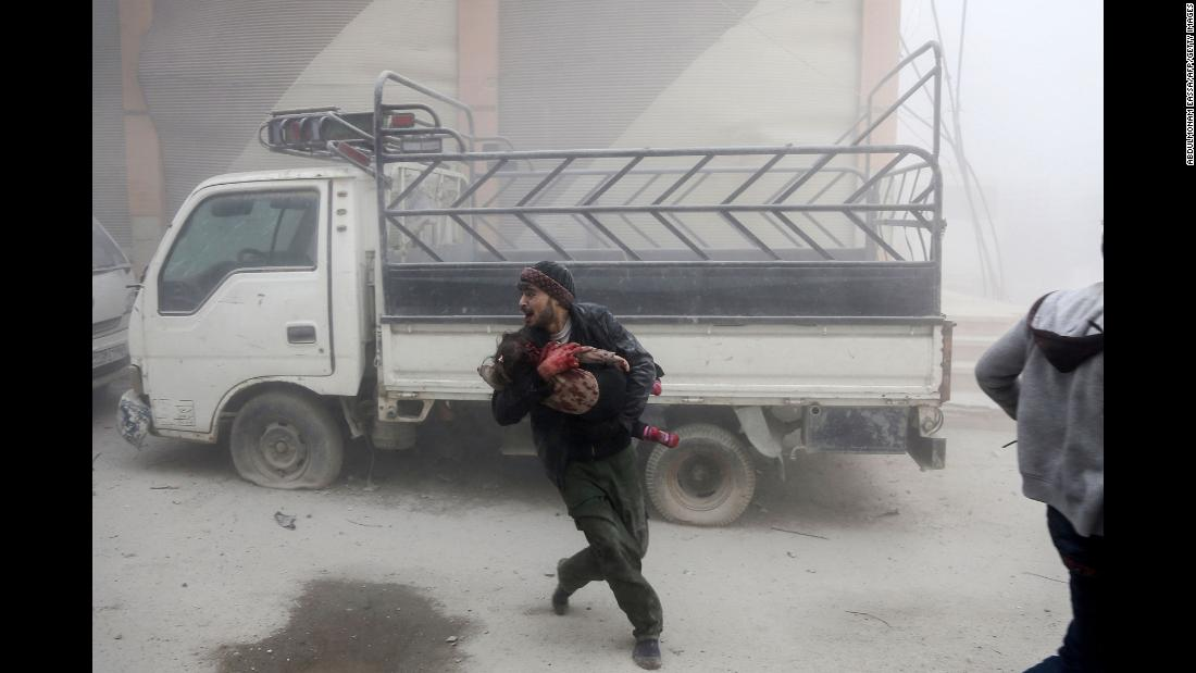 "A man carries a child as he flees from a reported Syrian airstrike in the rebel-held town of Saqba, in the Eastern Ghouta region of Syria, on Tuesday, February 6. More than 200 civilians have been killed since Monday, February 5, in <a href=""http://www.cnn.com/2018/02/08/middleeast/syria-eastern-ghouta-airstrikes/index.html"" target=""_blank"">Syrian government airstrikes on parts of Eastern Ghouta</a> near Damascus, the Syrian Observatory for Human Rights said. Among the deaths were 54 children and 41 women."