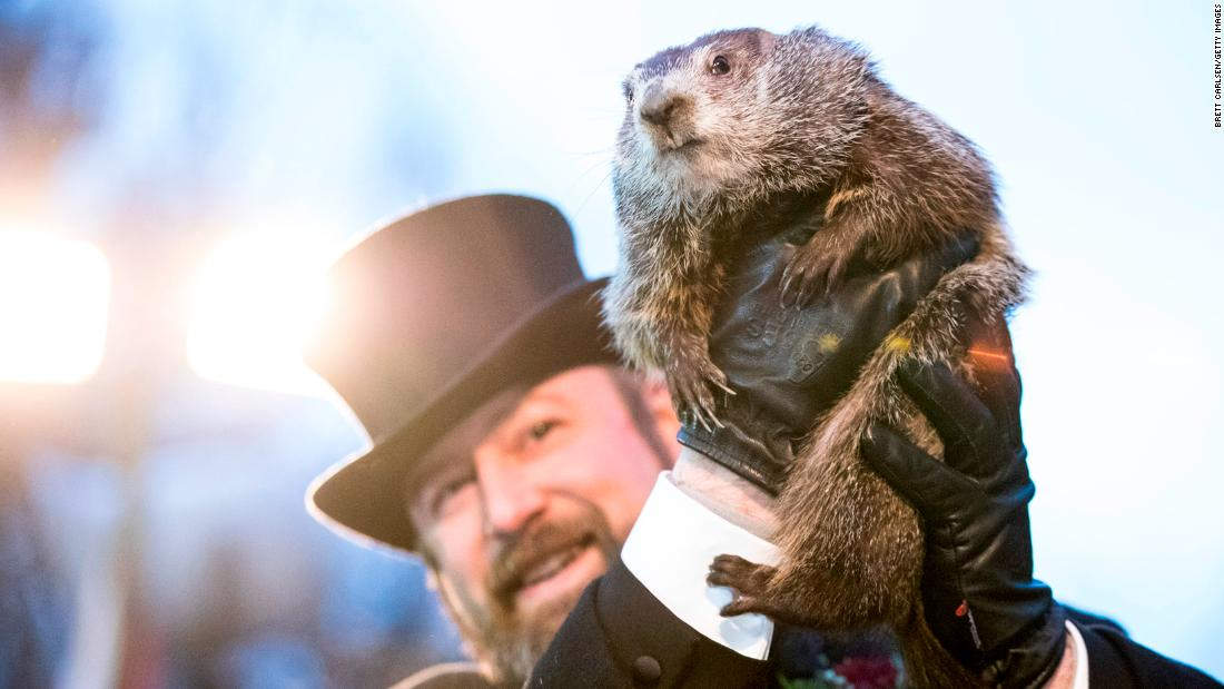 "Punxsutawney Phil is held up by his handler during the Groundhog Day ceremony in Punxsutawney, Pennsylvania, on Friday, February 2. <a href=""https://www.cnn.com/2018/02/02/us/groundhog-day-2018-shadow-trnd/index.html"" target=""_blank"">Punxsutawney Phil saw his shadow</a>, an omen indicating six more weeks of winter."