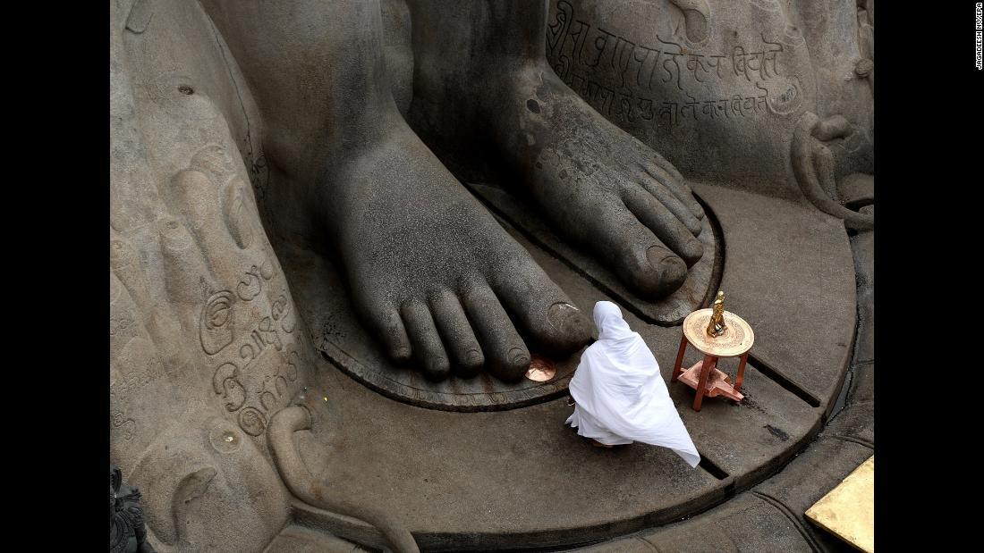 "A Jain nun offers prayers at the statue of Lord Bahubali during the <a href=""http://mahamasthakabhisheka.com/"" target=""_blank"">88th Bahubali Mahamasthakabhisheka Mahotsava ceremony</a> in Shravanabelagola, India, on Wednesday, February 7. The town  will attract millions of people from across the country for the head-anointing ceremony of the 57-foot-tall statue. The Jain ritual will run from February 7 to 26 and is held once every 12 years."