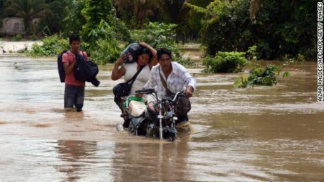 A family wades through a flooded highway, following the overflowing of the Beni river and heavy rains hitting the country, in Reyes, department of Beni, northeast Bolivia, on February 2, 2014. The Bolivian government has declared national emergency due to floodings which, up to now, have left more than 40 dead and about 33,000 families affected.    AFP PHOTO / Aizar Raldes        (Photo credit should read AIZAR RALDES/AFP/Getty Images)