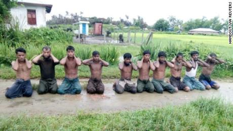 Ten Rohingya Muslim men with their hands bound kneel in Inn Din village September 1, 2017. Picture taken September 1, 2017.  Handout via REUTERS