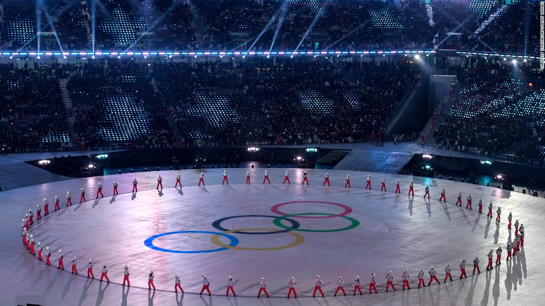 Participants perform around a design of the Olympic rings.