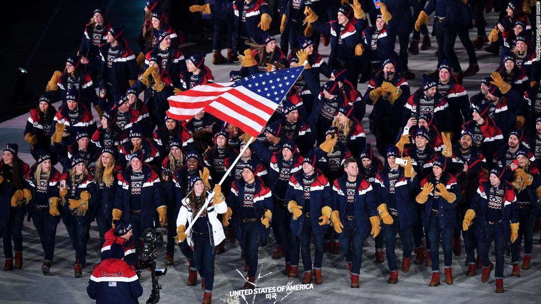 Luger Erin Hamlin carries the American flag as she leads US athletes during the Winter Olympics' opening ceremony on Friday, February 9. Hamlin is a four-time Olympian who won bronze in 2014.