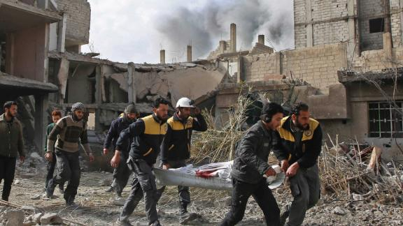 Syrian civil defense forces evacuate a victim of an air strike in the rebel-held enclave of Hazeh  on February 8, 2018.