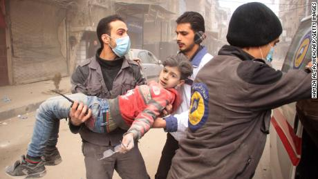 Members of Syrian Civil Defence carry an injured child following regime air strikes on the rebel-held besieged town of Douma in the eastern Ghouta region, on the outskirts of the capital Damascus, on February 7, 2018. / AFP PHOTO / Hamza Al-Ajweh        (Photo credit should read HAMZA AL-AJWEH/AFP/Getty Images)