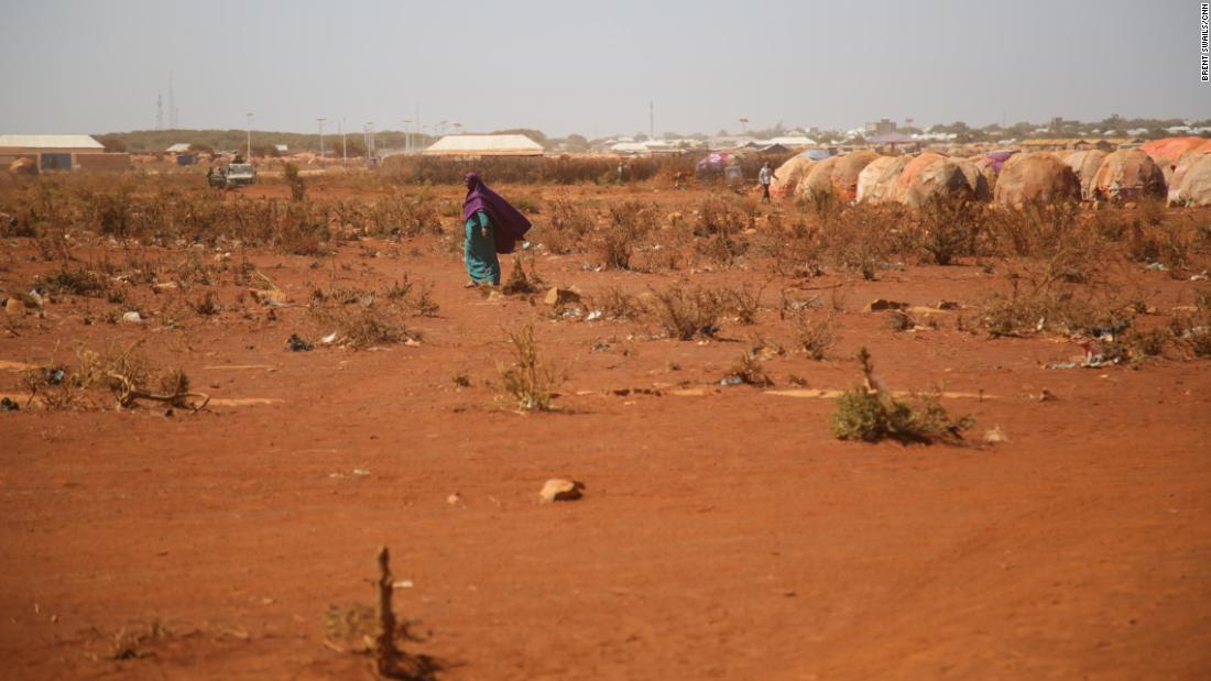 An internally displaced woman walks near a refugee camp in Baidoa.