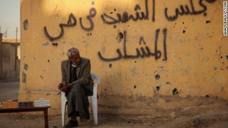"A man sitting under a graffiti that says ""the people's council in Al-Mashlib neighbourhood"" at the side of a street in Al-Mashlib neighbourhood in Raqqa city, Syria."