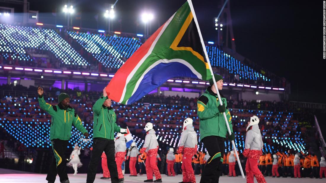 Flag bearer Connor Wilson of South Africa leads the team during the Opening Ceremony. The alpine skier is the sole representative for South Africa in the Winter Olympics.