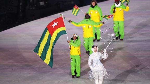 Flag bearer Mathilde-Amivi Petitjean of Togo is accompanied by her team. The second athlete for Togo Alessia Afi Dipol is an Italian alpine skier.
