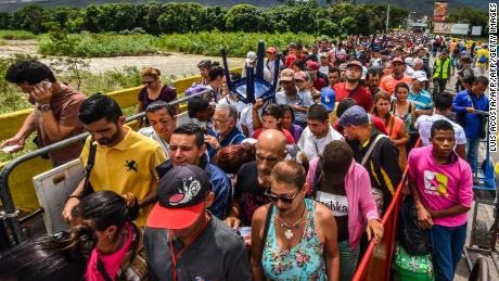 TOPSHOT - Venezuelan citizens enter Cucuta, Norte de Santander Department, Colombia from San Antonio del Tachira, Venezuela at the Simon Bolivar international bridge on July 25, 2017. Some 25.000 Venezuelans cross to Colombia and return to their country daily with food, consumables and money from ilegal work, according to official sources. Also, there are 47.000 Venezuelans in Colombia with legal migratory status and another 150.000 who have already completed the 90 allowed days and are now without visa.  / AFP PHOTO / Luis Acosta        (Photo credit should read LUIS ACOSTA/AFP/Getty Images)