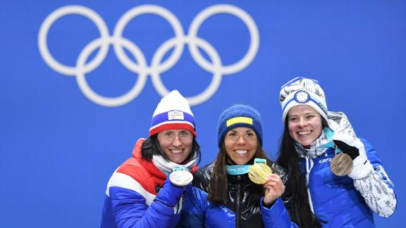 Sweden's Charlotte Kalla, center, celebrates after winning the first gold medal of the 2018 Winter Olympics. She finished first in the 15-kilometer cross-country ski event. Norway's Marit Bjørgen, left, won the silver to become the most decorated woman in the history of the Winter Games. Finland's Krista Parmakoski took the bronze.
