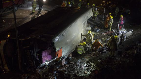 Firefighters dig through  debris after a deadly bus crash on Saturday in Hong Kong.