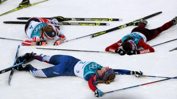 The United States' Jessica Diggins collapses alongside her competitors after competing in cross-country skiing.